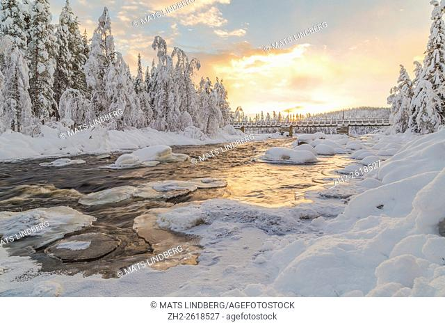 Wassara river with old wooden bridge, open water, sun reflecting in the water, snowy trees and snow on the rocks in the water, Gällivare, Swedish Lapland