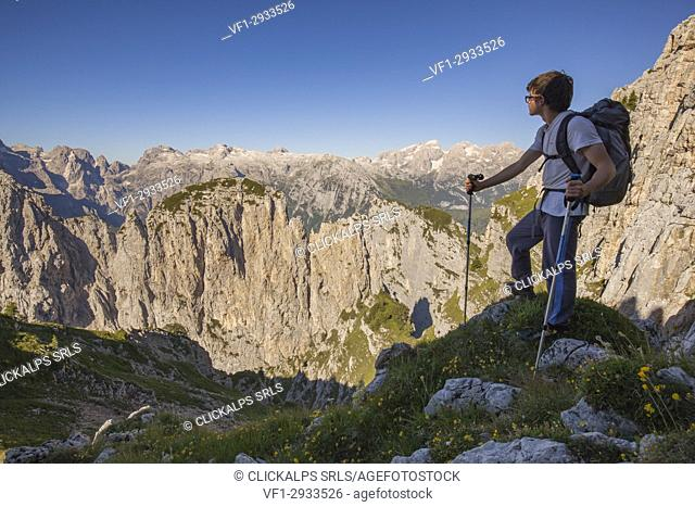 Hikers at Passo del Ciodo admire the panorama to the steep walls of the Third and Fourth Pala. In the background the plateau of the Pale di San Martino