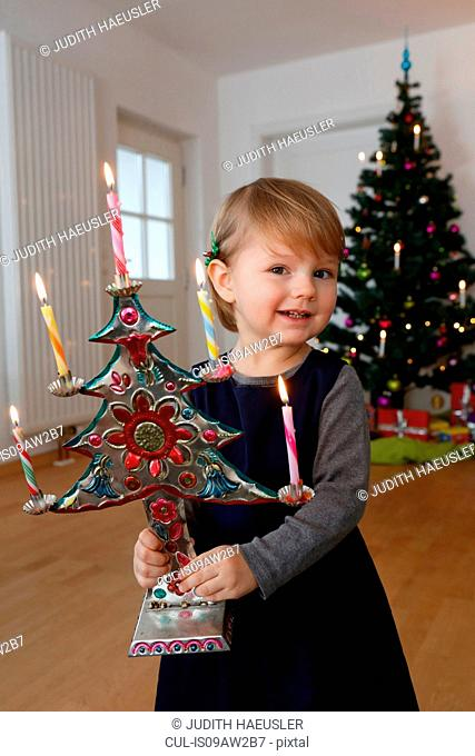 Girl in front of christmas tree holding christmas ornament looking at camera smiling