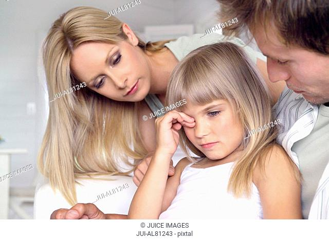 Parents talking to sad daughter of sofa