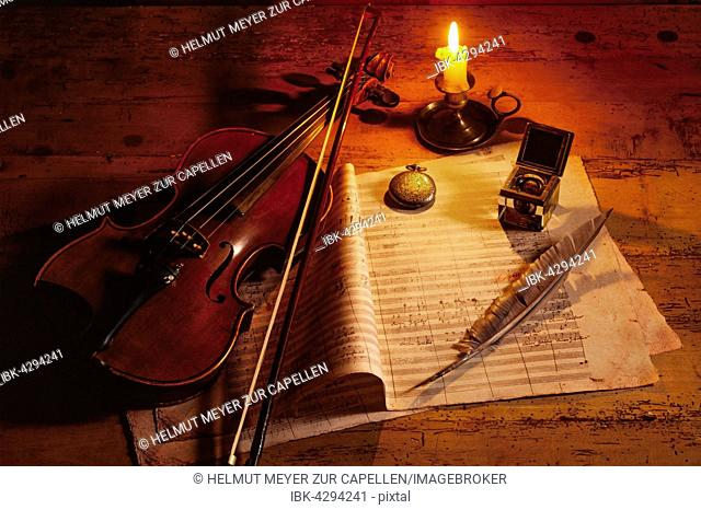 Violin with music sheet and quill by candlelight