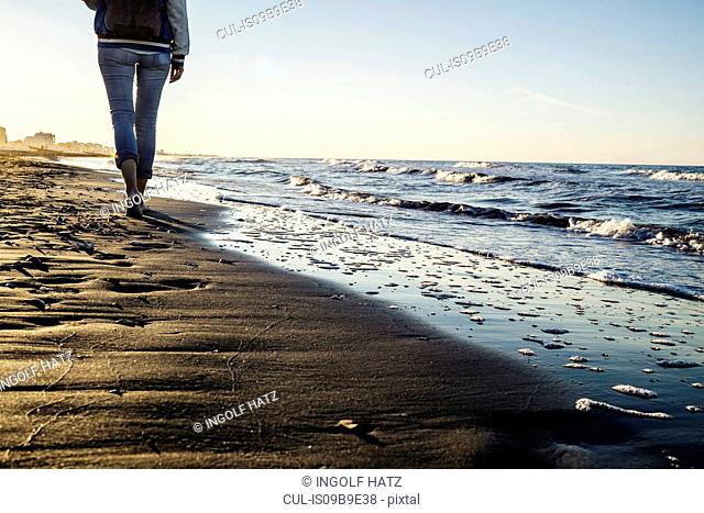 Waist down view of barefooted woman strolling along water's edge on beach, Riccione, Emilia-Romagna, Italy