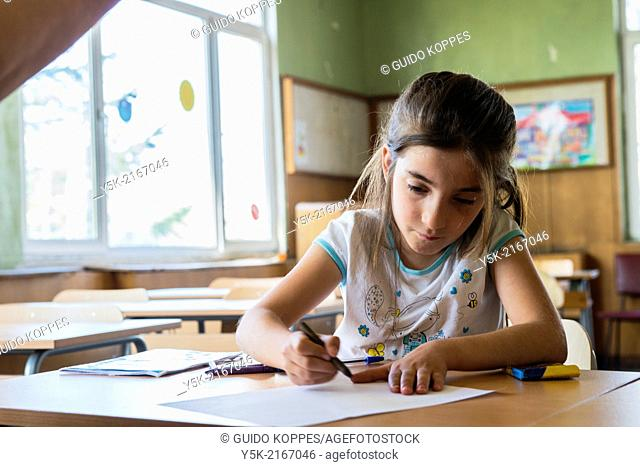 Sofia, Bulgaria. Syrian refugee school girl making a drawing in her camp school class