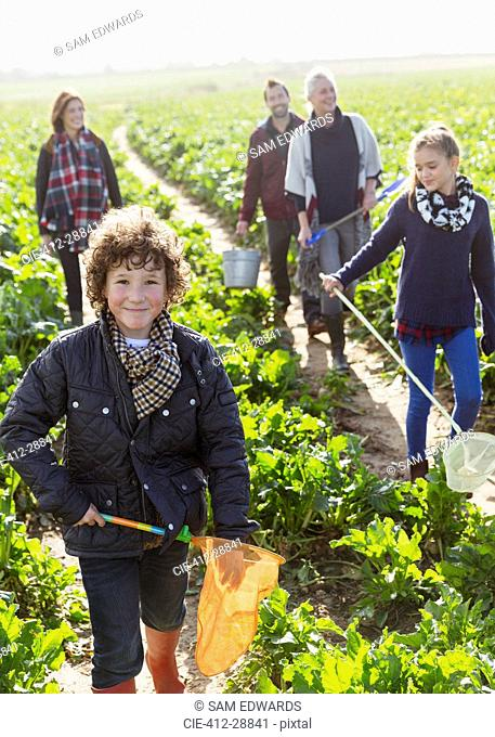 Portrait smiling boy with net walking in vegetable garden with family