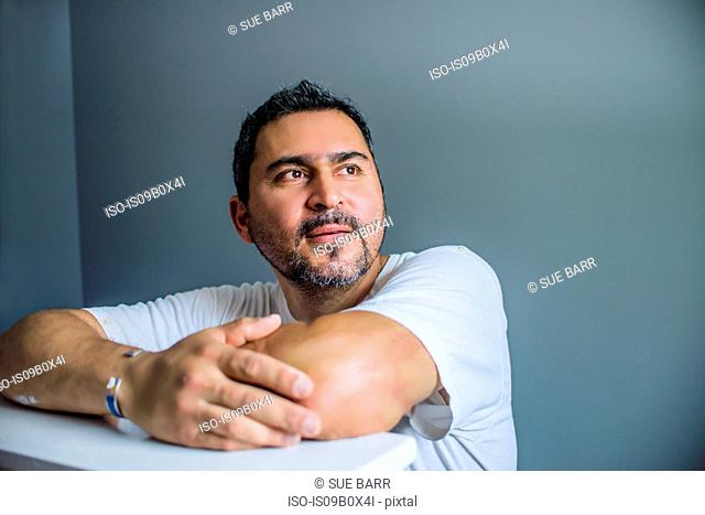 Man resting on elbows looking away