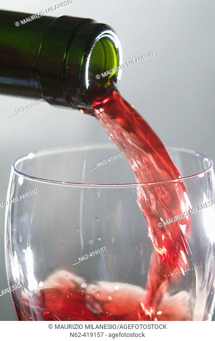 Someone from a green bottle pouring red wine into a wine glass
