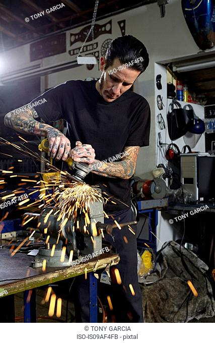 Mature man welding parts in motorcycle repair workshop