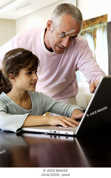 Father helping daughter on laptop