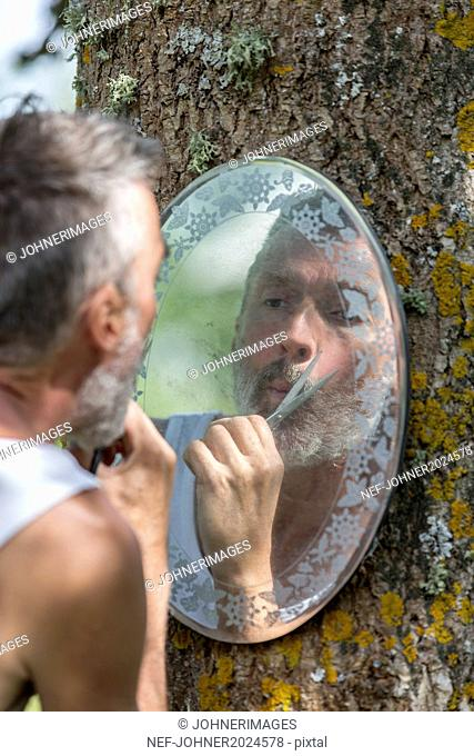 Mature man trimming beard