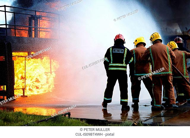 Firemen training to put out fire on burning building, Darlington, UK