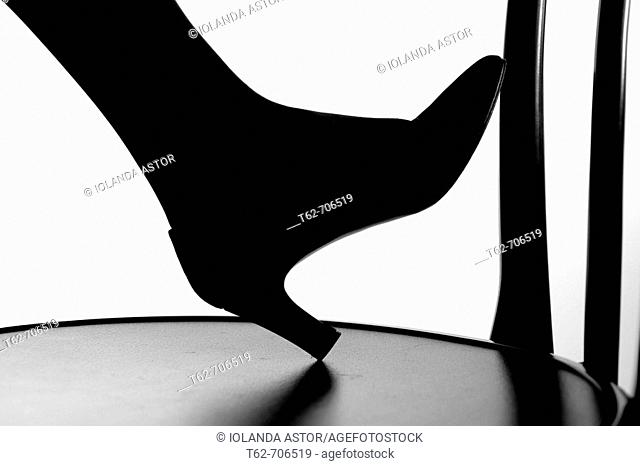 Silhouette against the foot of a woman's shoe in high-heeled shoe