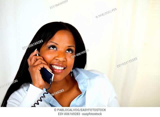 Close up portrait of a pretty woman smiling and conversing on phone
