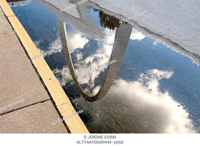 USA, Missouri, St. Louis, Gateway Arch reflected in a puddle