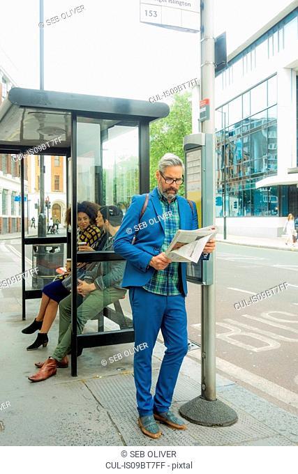 Man waiting at bus stop, London, UK