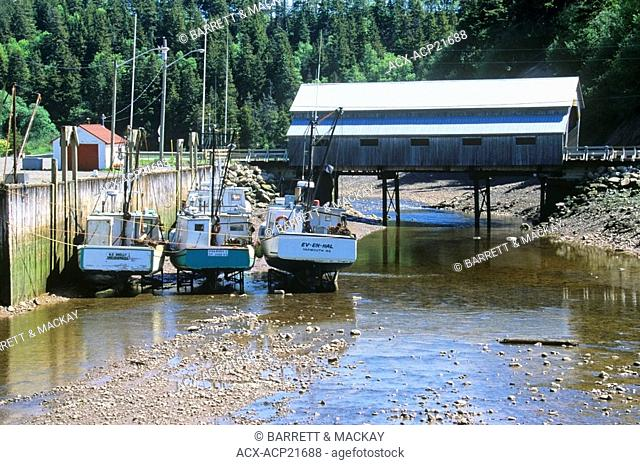 Fishing boats docked at low tide in front of covered bridge, St. Martins, Bay of Fundy, New Brunswick, Canada