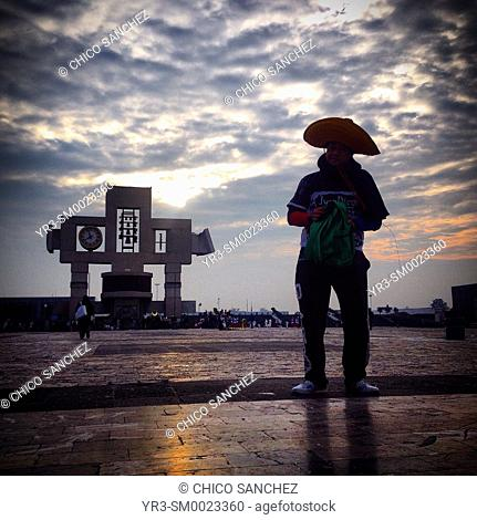A man wearing a Mexican stands in front of a cross during the annual pilgrimage to the Our Lady of Guadalupe basilica in Mexico City, Mexico