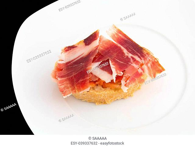 Plate of jabugo ham tapa with tomato slices and bread