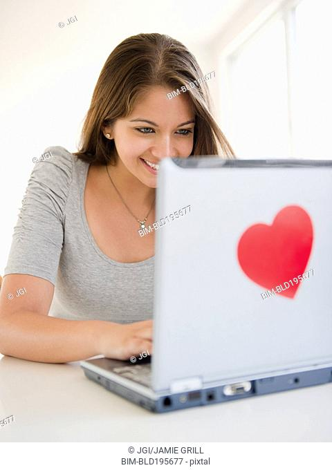 Indian woman using laptop with heart-shaped sticker