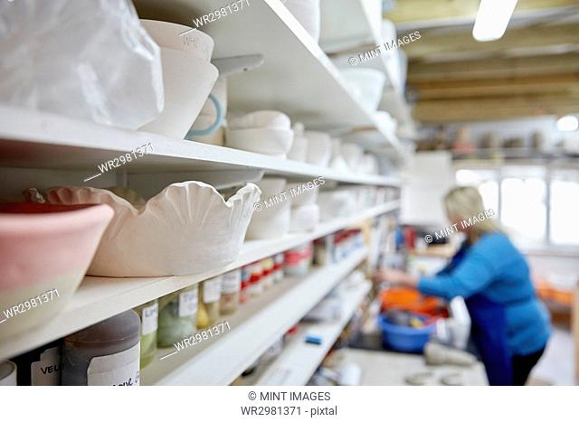 A woman working at a bench in a pottery studio. Shelves storing pots and bowls