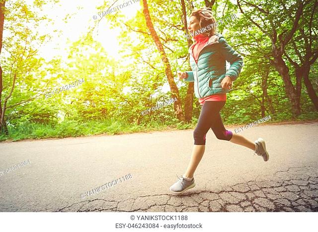 Young fitness blonde woman in headphones running at morning caucasian forest trail in sun light