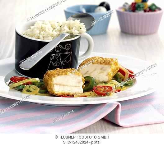 Baked coalfish with a cornflake coating served with vegetables and rice