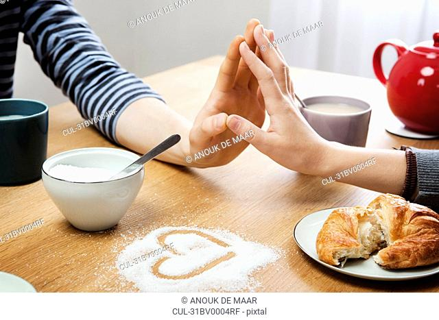Two hands touching over table