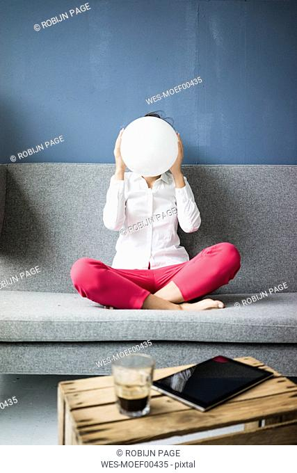 Woman sitting on couch hiding her face behind a white sphere