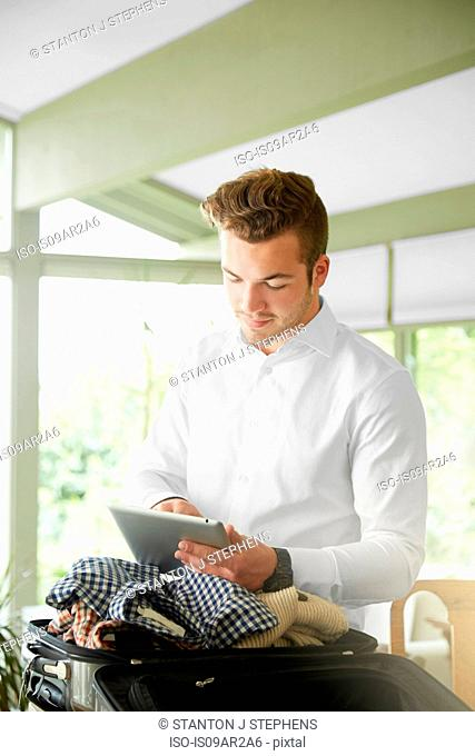 Businessman packing suitcase at home reading digital tablet