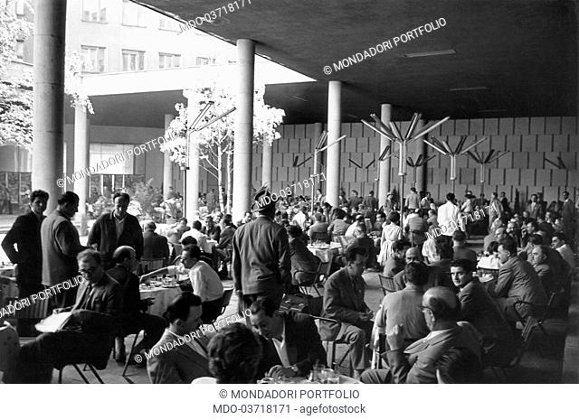 A crowd of people sitting outdoor at the tables of a café. Yugoslavia, May 1968
