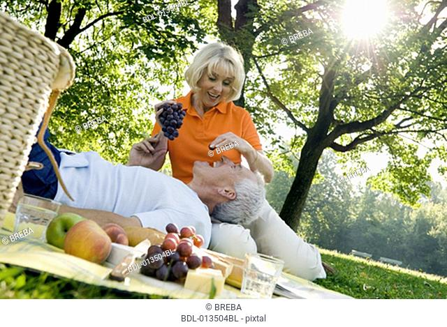 mature couple playing with grapes during picnic