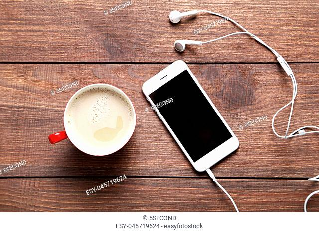 Cup of coffee and smarphone on a brown wooden table