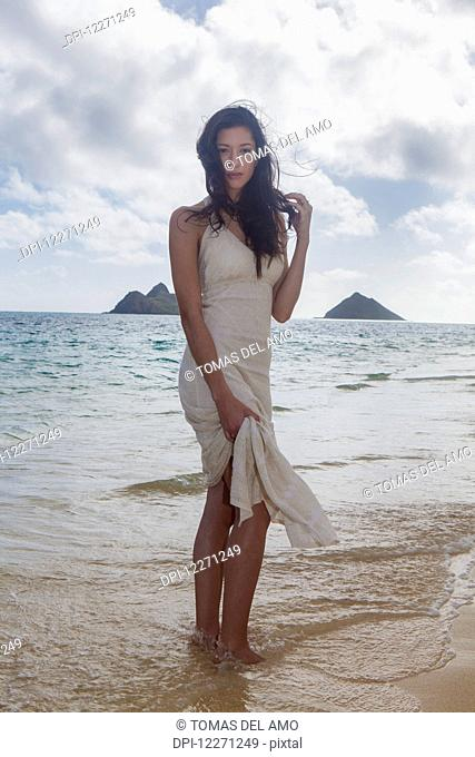 Young woman in white dress on the beach at the water's edge; Kailua, Island of Hawaii, Hawaii, United States of America