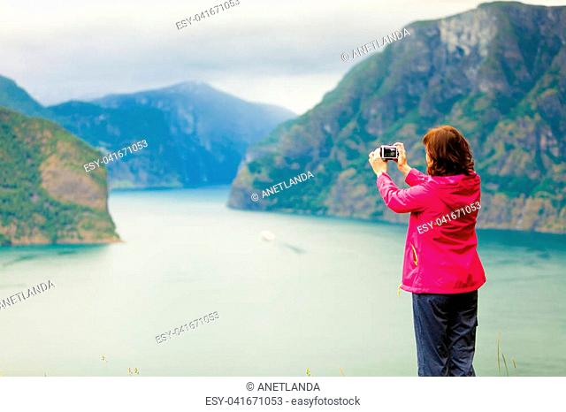 Tourism and travel. Woman tourist taking photo with camera, enjoying mountains fjords view in Sogn og Fjordane county. Norway Scandinavia