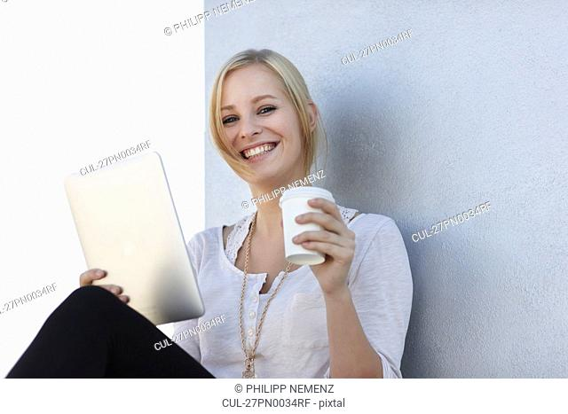 Women smiling with coffee and ipad