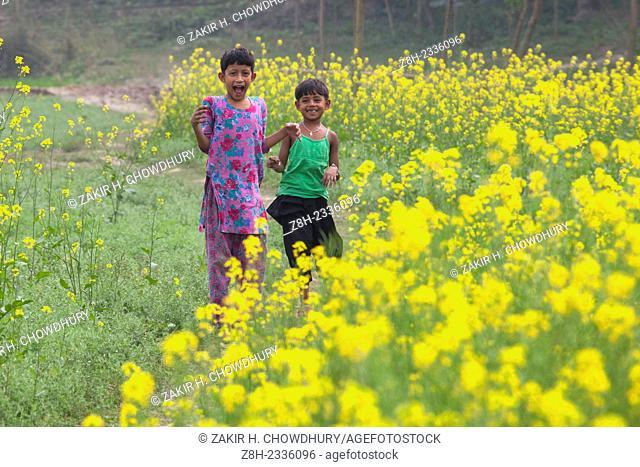 CHildren playing in mustard field in Bangladesh