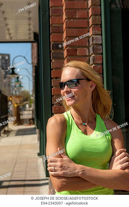 39 year old blond woman wearing fitness clothing and sunglasses in an urban setting