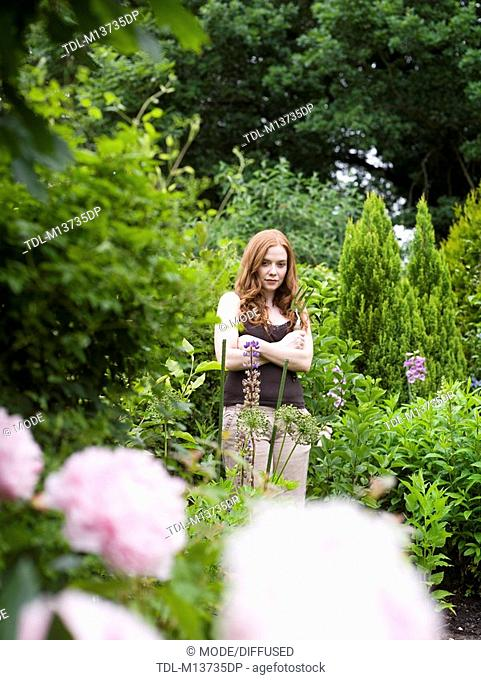 A woman standing in a garden with arms folded