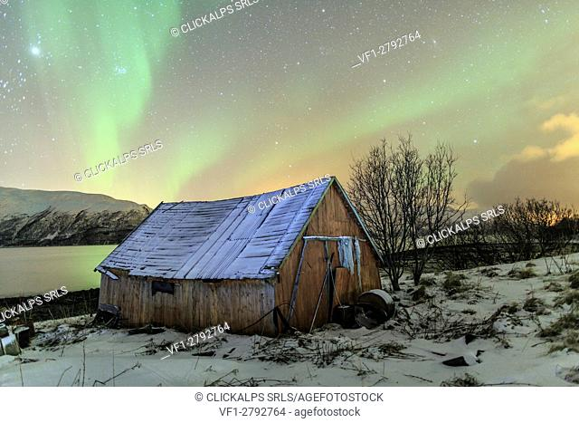The Northern Lights illuminates the wooden cabin Svensby Lyngen Alps Tromsø Lapland Norway Europe