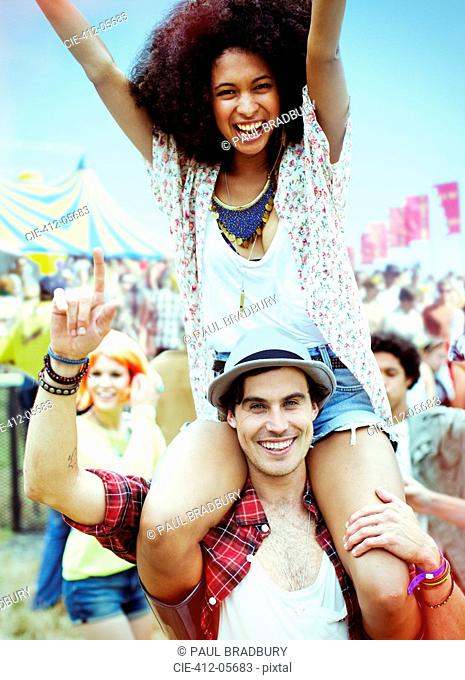 Portrait of man carrying enthusiastic woman on shoulders at music festival