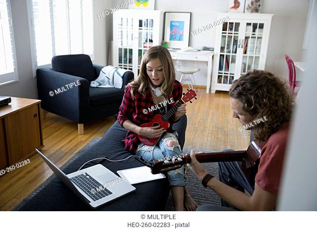 Couple playing guitar and ukulele in living room