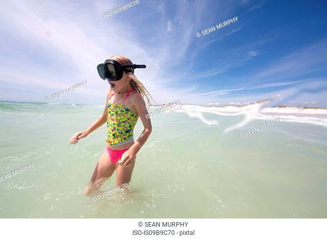 Girl with swim goggles wading in sea
