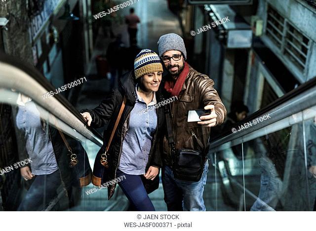 Couple on escalator taking a selfie