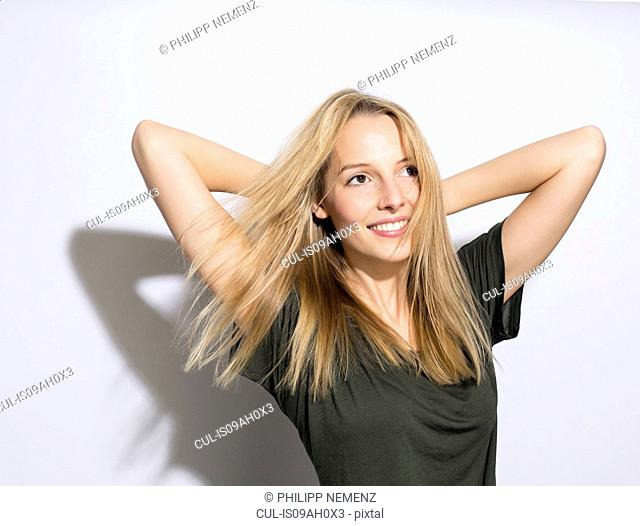 Young woman with long blonde hair, hands behind head