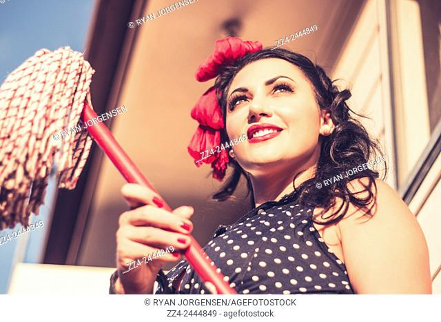 Old-fashioned photo of an attractive young brunette housewife holding red mop end on the verandah of a sixties home. Classic historical cleaners