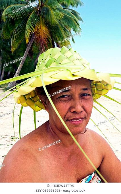 Portrait of Polynesian Pacific Island Tahitian mature female wearing here handcraft of a hat knees out of palm leaveson tropical beach in Aitutaki lagoon Cook...