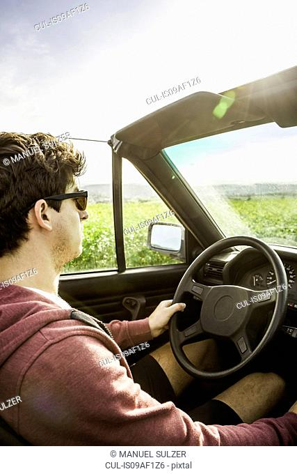 Young man leaning driving convertible