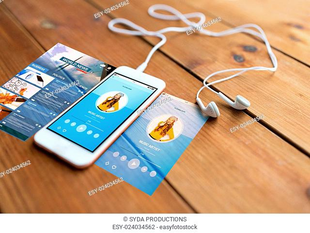 technology, music, gadget and object concept - close up of white smartphone and earphones on wooden surface with media player on screen