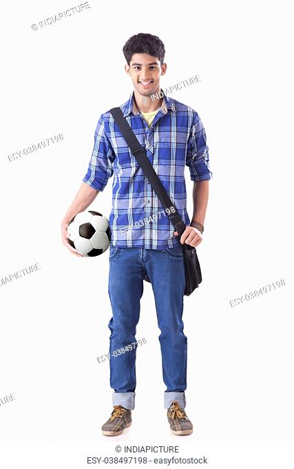 Portrait Of Smiling Young Student Holding Football And Carrying Hand Bag