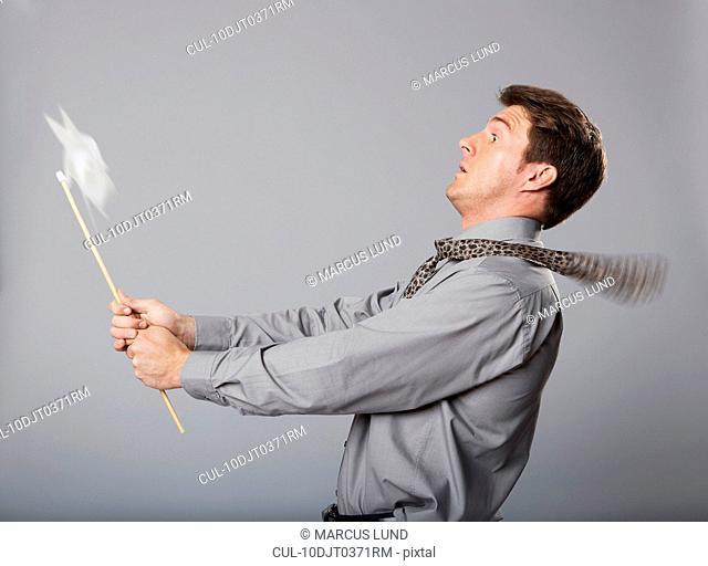 Business man holding windmill