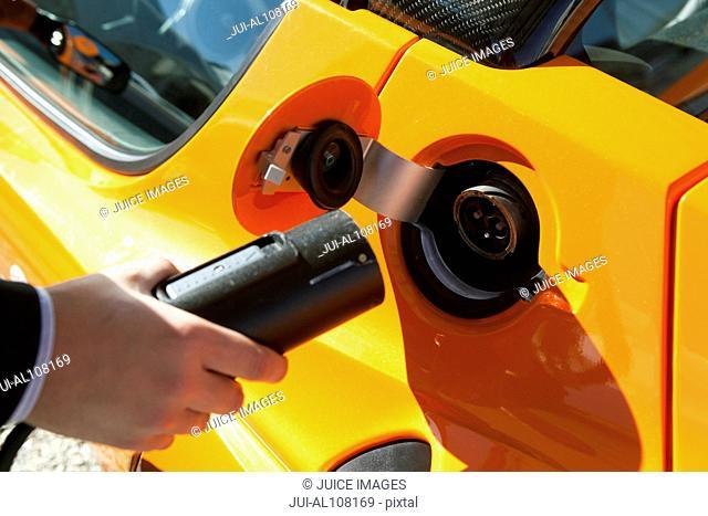 Close-up of man charging electrical car